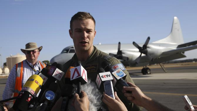 In this photo provided by China's Xinhua News Agency, Royal Australian Air Force (RAAF) Flight Lt. Russell Adams who piloted the P-3 Orion search and rescue aircraft speaks to the media after he returned from their search operation for the missing Malaysia Airlines flight MH370, at Pearce Airbase near Perth, Australia, Friday, March 21, 2014. Search planes scoured a remote patch of the Indian Ocean but came back empty-handed Friday after a 10-hour mission looking for any sign of the missing Malaysia Airlines jet, another disappointing day in one of the world's biggest aviation mysteries. (AP Photo/Xinhua, Xu Yanyan) NO SALES