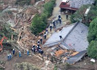 Rescuers search destroyed houses for missing people after a landslide triggered by Typhoon Talas that brought heavy rains at Tanabe, central Japan, Monday, Sept. 5, 2011. The storm dumped record amounts of rain Sunday in western and central Japan as it turned towns into lakes, washed away cars and triggered mudslides that obliterated houses. (AP Photo/Kyodo News) JAPAN OUT, MANDATORY CREDIT, NO LICENSING IN CHINA, FRANCE, HONG KONG, JAPAN AND SOUTH KOREA
