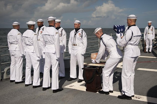 U.S. Navy personnel carry the remains of Apollo 11 astronaut Neil Armstrong during a burial at sea service aboard the USS Philippine Sea (CG 58), Friday, Sept. 14, 2012, in the Atlantic Ocean. Armstrong, who died last month in Ohio at age 82, walked on the moon in July 1969. (AP Photo/NASA, Bill Ingalls)