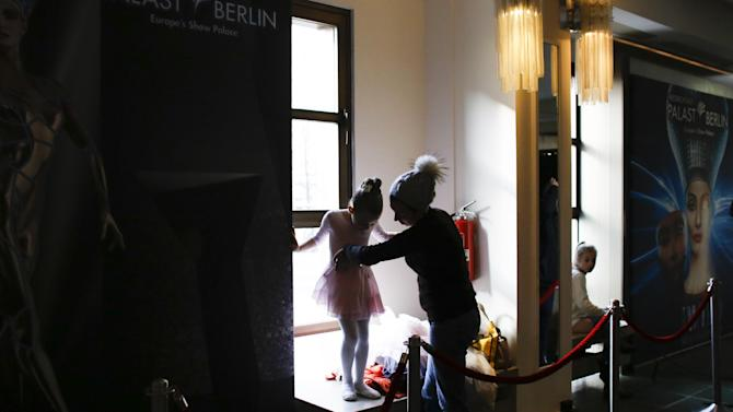 In this photo taken Wednesday, Feb. 18, 2015, a mother helps her daughter to dress up for the first round of a casting for the the Young Ensemble of the Friedrichstadt-Palast Theatre in Berlin, Germany. Hundreds of children apply every year for only 20-30 spots in the theater's renowned Young Ensemble.  Overall, some 250 children, ages seven through 16, attend the school at any one time. The ensemble provides year-round theatre training for children. All children receive two years of basic training in classic dance, drama and jazz. (AP Photo/Markus Schreiber)