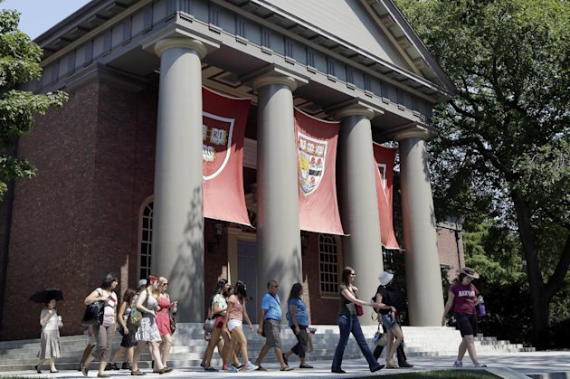 People are led on a tour group at the campus of Harvard University in Cambridge, Mass. Thursday, Aug. 30, 2012. Dozens of Harvard University students are being investigated for cheating after school officials discovered evidence they may have wrongly shared answers or plagiarized on a final exam. Harvard officials on Thursday didn't release the class subject, the students' names, or specifically how many are being investigated. (AP Photo/Elise Amendola)