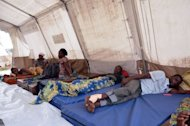 People wounded in blasts at an arms depot in Brazzaville sit in a tent set up near the city&#39;s main hospital emergency unit. The death toll from powerful explosions at a Congo munitions dump approached 200 on Tuesday, as international aid began to arrive to help treat over 1,300 wounded and assist 5,000 homeless