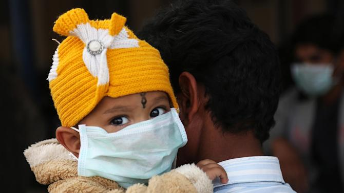An Indian child, wearing a mask as preventive measures against swine flu, is carried by an adult inside Gandhi Hospital premise in Hyderabad, India, Saturday, Jan. 31, 2015. Swine flu has claimed more than 20 lives in the Hyderabad region in the month of January, according to Indian news reports. (AP Photo/Mahesh Kumar A.)