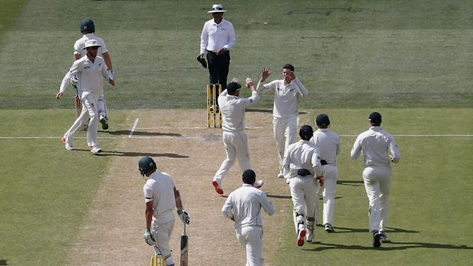 New Zealand's Santner celebrates with team mates after bowling Australia's Hazlewood for four runs during the second day of the third cricket test match at the Adelaide Oval, in South Australia