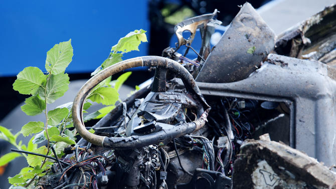 A view of the driving wheel of a bus which crashed off a highway near Avellino, southern Italy, Monday, July 29, 2013. Rescuers wielding electric saws cut through the twisted wreckage of an Italian tour bus for survivors of a crash in southern Italy that killed at least 37 people after it crashed into traffic and plunged into a ravine on Sunday night. Reports said as many as 49 people, mostly Italians, had been aboard the bus when it ripped through a guardrail, then plunged some 30 meters (100 feet) off a viaduct near a wooded area. (AP Photo/Salvatore Laporta)