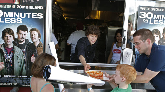 """A photo provided by Moroch shows actor Jesse Eisenberg handing out slices of pizza at Home Slice Pizza in Austin, Texas, Monday July 11, 2011.  Eisenberg stars in new comedy film """"30 Minutes or Less,"""" directed by Ruben Fleischer. (AP Photo/Moroch, Erich Schlegel)"""
