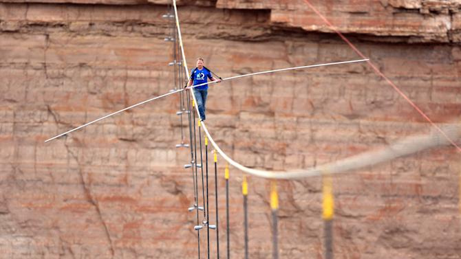 In this photo provided by the Discovery Channel, aerialist Nik Wallenda walks a 2-inch-thick steel cable taking him a quarter mile over the Little Colorado River Gorge, Ariz. on Sunday, June 23, 2013. The daredevil successfully traversed the tightrope strung 1,500 feet above the chasm near the Grand Canyon in just more than 22 minutes, pausing and crouching twice as winds whipped around him and the cable swayed. (AP Photos/Discovery Channel, Tiffany Brown)