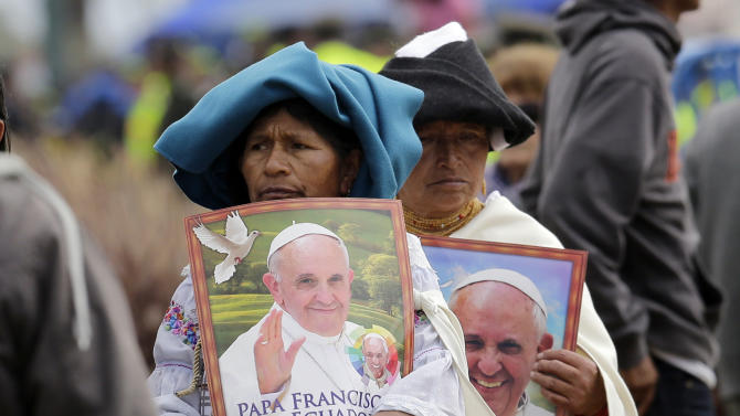 Otavalenas Indians holding posters featuring Pope Francis arrive at Bicentennial Park to attend a Mass celebrated by the pontiff, in Quito, Ecuador, Tuesday, July 7, 2015. The pope's final Mass in Ecuador featured readings in Quichua, the native language most spoken in Ecuador. (AP Photo/Dolores Ochoa)