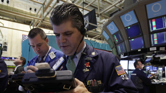 Traders Kevin Lodewick, left, and John Panin work on the floor of the New York Stock Exchange Wednesday, June 20, 2012. Stocks edged lower early Wednesday after investors saw signs that economies could be slowing down in both the West and China. (AP Photo/Richard Drew)