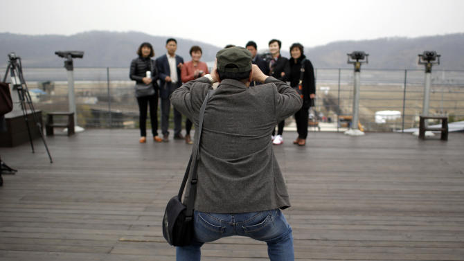 """Chinese tourists take pictures at the Imjingak Pavilion near the border village of Panmunjom, dividing the two Koreas since the Korean War, in Paju, north of Seoul, South Korea, Friday, April 5, 2013. After a series of escalating threats, North Korea has moved a missile with """"considerable range"""" to its east coast, South Korea's defense minister said Thursday. But he emphasized that the missile was not capable of reaching the United States and that there are no signs that the North is preparing for a full-scale conflict. (AP Photo/Lee Jin-man)"""