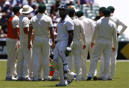 England's Carberry walks off the field after his dismissal, as Australia's team celebrates, during the third day of the second Ashes test cricket match in Adelaide