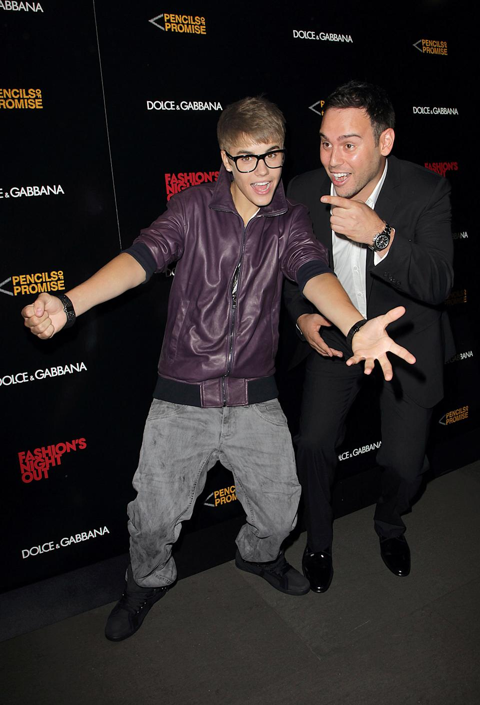 Singer Justin Bieber, left, and and Scooter Braun attend the Fashion Night Out Dolce & Gabbana at the Dolce & Gabbana store on Madison & 69th street on Thursday, Sept. 8, 2011. (AP Photo/Donald Traill)