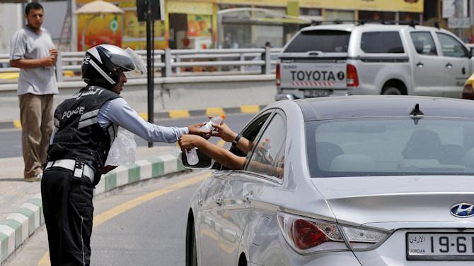 A Jordanian traffic police officer distributes cold water to drivers and passers-by during a heatwave in Amman