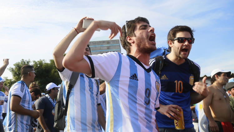 Argentina fans cheers, one day before their team's game against Nigeria, in Porto Alegre, Brazil, Tuesday, June 24, 2014. Authorities in this southern city, 430 miles from the Argentine border expected 80,000 Argentines to arrive for the World Cup match, only a quarter of them holding tickets for the game. While the fans had been good-natured so far, the city of about 1.4 million people was taking precautions. (AP Photo/Pedro Garcia)