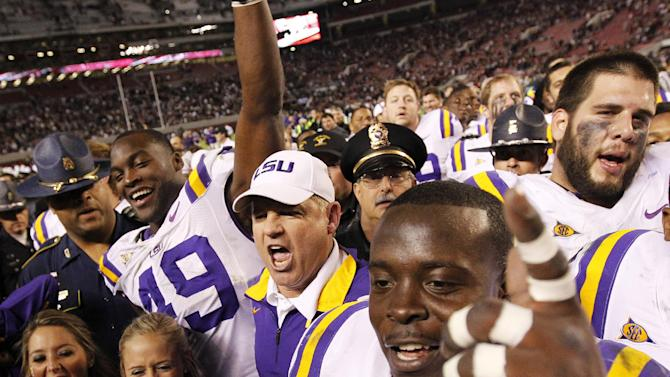 LSU head coach Les Miles celebrates with his team after the second half of an NCAA college football game against Alabama, Saturday, Nov. 5, 2011, in Tuscaloosa, Ala. LSU won 9-6 in overtime. (AP Photo/Dave Martin)