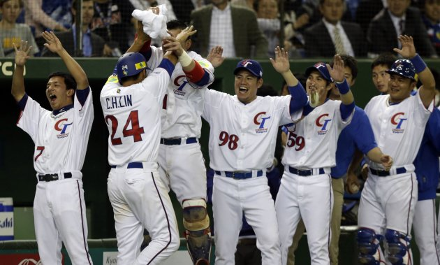 Taiwan's Lin celebrates with his teamates after scoring against Japan in the fifth inning at the WBC second round game in Tokyo