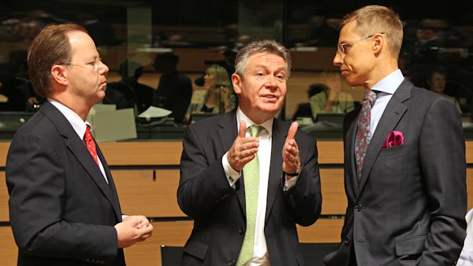 Dutch Economic Affairs Minister Henk Kamp, left, talks with European Commissioner for Trade Karel De Gucht, center, and Finnish Foreign Trade Minister Cai-Goran Alexander Stubb, during the EU Trade ministers meeting in Luxembourg, Friday June 14, 2013. France enters a key meeting of European Union trade ministers bent on keeping its audiovisual industry out of trans-Atlantic free trade negotiations, a move that would delay any opening of sweeping talks with the United States. (AP Photo/Yves Logghe)