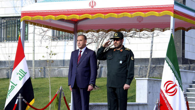 This photo released by the Iranian Defense Ministry shows, Iranian Defense Minister Hossein Dehghan, right, and his Iraqi counterpart Khalid al-Obeidi, as they listen to their countries national anthems during an official welcoming ceremony for al-Obeidi, in Tehran, Iran, Monday, Dec. 29, 2014. (AP Photo/Iranian Defense Ministry)