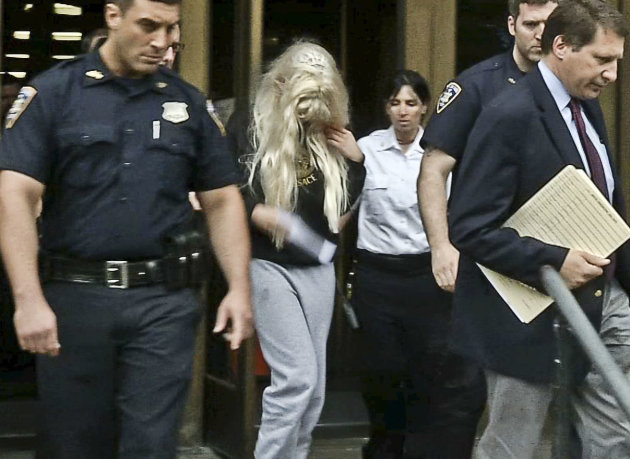 In an image made from video, actress Amanda Bynes, center, wearing sweats and a blonde wig, is escorted after a Manhattan criminal court appearance on Friday May 24, 2013 in New York.  Bynes was arres