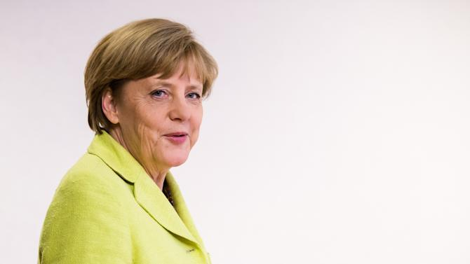 German Chancellor Angela Merkel arrives for a media conference at the end of an EU summit at the European Council building in Brussels, early Thursday, July 17, 2014. European Union leaders ordered tougher sanctions against Russia early Thursday because of its actions in Ukraine, asking the European Investment Bank to sign no new financing agreements with Moscow. The leaders, meeting in Brussels, also agreed to act together to suspend financing of the new European Bank for Reconstruction and Development operations in Russia. (AP Photo/Geert Vanden Wijngaert)
