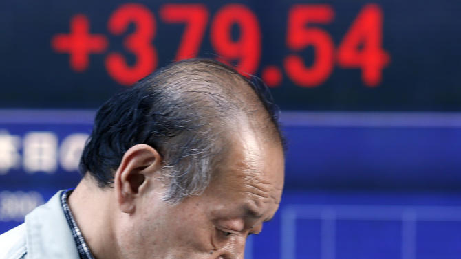 A man walks by an electronic stock board of a securities firm in Tokyo, Thursday, June 27, 2013. Stock markets from Sydney to Shanghai extended gains for a second day Thursday after the U.S. said quarterly growth may be weaker than expected, raising investors' hopes that the Federal Reserve would delay plans to wind down its stimulus program.(AP Photo/Koji Sasahara)