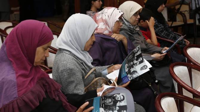 """Relatives of victims look at Human Rights Watch new report """"Just sign here"""" before a news conference inRabat, Morocco, Friday,June 21, 2013. Human Rights Watch says in a new report that Morocco's justice system overly relies on coerced confessions and needs serious reform. (AP Photo/Abdeljalil Bounhar)"""