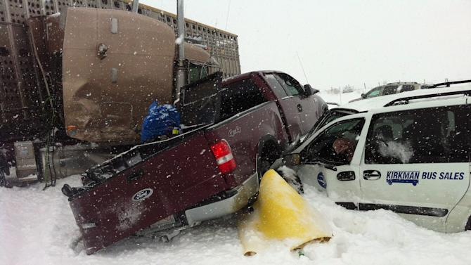 A pickup truck is sandwiched between two vehicles as more than 300 people have been injured following a multi-vehicle crash in snowy conditions Thursday, March 21, 2013 on Highway 2 south of Edmonton, Alberta. A blizzard sweeping across the Canadian plains caused a chain of traffic wrecks involving a bus, semi-trailer trucks and cars south of Edmonton, Alberta, sending about 300 injured travelers to hospitals on Thursday, officials said. (AP Photo/The Canadian Press, Derek Fildebrandt)