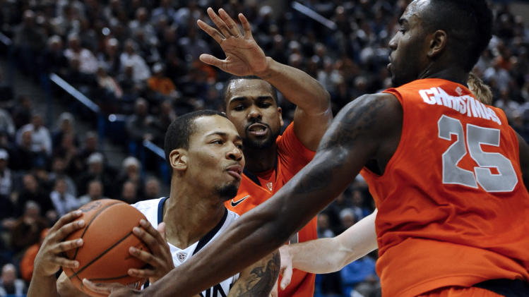 Connecticut's Omar Calhoun, left, is pressured by Syracuse's James Southerland, center, and Syracuse's Rakeem Christmas, right, during the second half of an NCAA college basketball game in Hartford, Conn., Wednesday, Feb. 13, 2013. Connecticut won 66-58. (AP Photo/Jessica Hill)