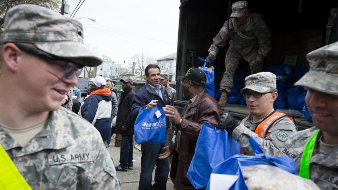 New York Governor Andrew Cuomo assists the National Guard unload a truck of supplies in the Far Rockaways section of the Queens borough of New York, Saturday, Nov. 10, 2012.  Despite power returning to many neighborhoods in the metropolitan area, residents of the Far Rockaways continue to live without power and heat due to damage caused by Superstorm Sandy.(AP Photo/John Minchillo)