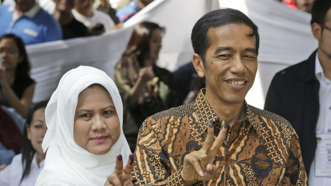 "Indonesian presidential candidate Joko Widodo, popularly known as ""Jokowi"", left, and his wife Iriana, show their inked fingers after casting their ballots during the presidential election in Jakarta, Indonesia, Wednesday, July 9, 2014. As the world's third-largest democracy began voting Wednesday to elect a new president, Indonesians are divided between two very different choices: a one-time furniture maker, Jakarta Governor Joko Widodo, and a wealthy ex-army general with close links to former dictator Suharto, Prabowo Subianto. (AP Photo/Dita Alangkara)"