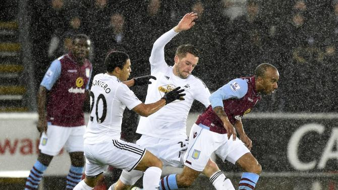 Swansea City's Gylfi Sigurdsson (C) challenges Aston Villa's Fabian Delph ( R) during their English Premier League soccer match at the Liberty Stadium in Swansea