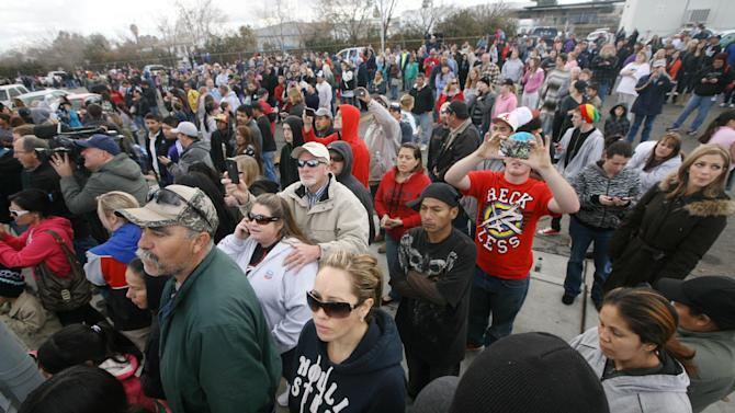 Parents and students gather outside Taft Union High School after a shooting on Thursday, Jan. 10, 2012 in Taft, Calif.   The sheriff of Kern County, Calif., says a 16-year-old student shot at a high school is in critical but stable condition. Sheriff Donny Youngblood says the shooter is a student who walked into a class at Taft Union High School Thursday morning and shot the teen with a shotgun, and then fired at another student but missed. A teacher suffered a minor pellet wound to the head. Youngblood says the teacher tried to get other students out a back door, then he and another staff member engaged the shooter in conversation to distract him, and convinced him to put down the gun. (AP Photo/The Bakersfield Californian, Alex Horvath)  MANDATORY CREDIT; MAGS OUT; NO SALES; ONLINE OUT; TV OUT