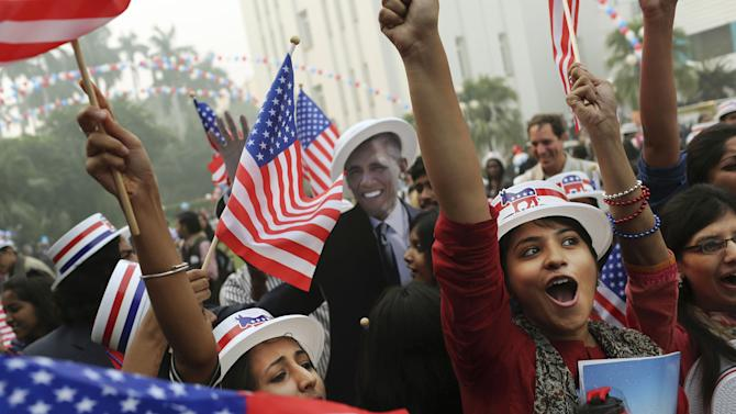 Indian students react in front of photographers next to a cardboard cutout of President Barack Obama after he was projected as the winner of the U.S. presidential election during an event organized by the U.S. Embassy at the landmark Imperial Hotel in New Delhi, India, Wednesday, Nov. 7, 2012. Obama captured a second White House term, blunting a mighty challenge by Republican Mitt Romney as Americans voted for a leader they knew over a wealthy businessman they did not. (AP Photo/Kevin Frayer)