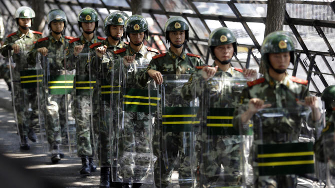 Chinese paramilitary police march with their shields outside the entrance to the Japanese Embassy in Beijing, China, Wednesday, Sept. 19, 2012. People across China have engaged in days of furious protests over some East China Sea islands, claimed by Beijing and Tokyo, that Japan purchased last week from a private owner. (AP Photo/Ng Han Guan)