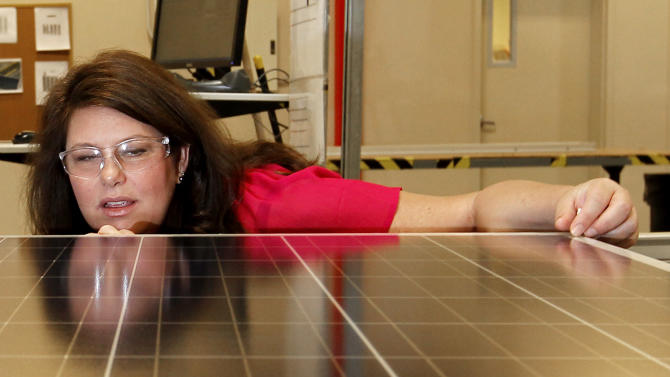 In this Sept. 4, 2012 photo, Stacey Rassas, a quality control manager at Suntech Power Holdings Co., a Chinese-owned solar panel manufacturer, examines a solar panel at a company facility in Goodyear, Ariz. The factory makes solar panels for one of the world's biggest solar manufacturers. (AP Photo/Ross D. Franklin)