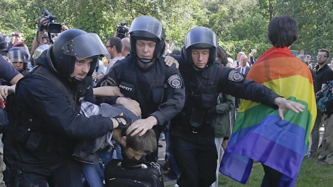 Riot police detain a protester who is trying to stop Ukraine's first gay pride demonstration in Kiev, Ukraine, Saturday, May 25, 2013. About a hundred gay and lesbian Ukrainians and those from other countries took part in the gay pride rally, protected by hundreds of riot police. Antipathy toward homosexuals remains strong in Ukraine. (AP Photo/Efrem Lukatsky)