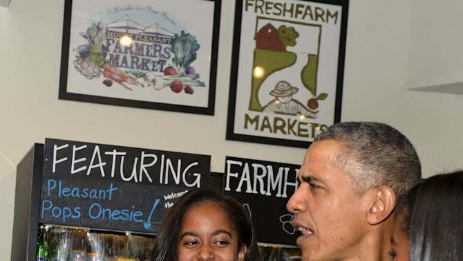 U.S. President Barack Obama chats with workers at Pleasant Pops next to his daughters Sasha and Malia in Washington