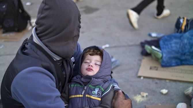 A Syrian refugee man holding his sleeping son, rests on the ground after spending the night at a collection point in the truck parking lot of the former border station on the Austrian side of the Hungarian-Austrian border near Nickelsdorf, Austria, Wednesday, Sept. 23, 2015. European Union ministers agreed Tuesday to relocate 120,000 migrants in a move intended to ease the strain on nations Greece and Italy which are on the frontline of the continent's overwhelming migrant crisis. (AP Photo/Muhammed Muheisen)