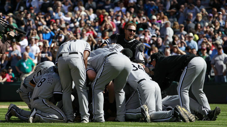 Chicago White Sox starting pitcher Phil Humber is mobbed after pitching a perfect baseball game against the Seattle Mariners, Saturday, April 21, 2012, in Seattle. The White Sox won 4-0. (AP Photo/Elaine Thompson)