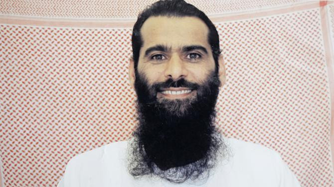In this undated photo taken by the International Red Cross and provided by the family of Muhammed Rahim al-Afghani, Muhammed Rahim al-Afghani poses for a photo at Guantanamo Bay prison at the U.S. Naval Base in Cuba. Rahim who is being held with the most significant terrorism suspects in U.S. custody has apparently gained extensive knowledge of western pop culture in Guantanamo's Camp 7: the top secret prison-within-a-prison in Guantanamo Bay. Nearly five years ago, Rahim became the last prisoner sent to Guantanamo. He was accused of helping Osama bin Laden elude capture. (AP Photo/International Red Cross via Rahim family)