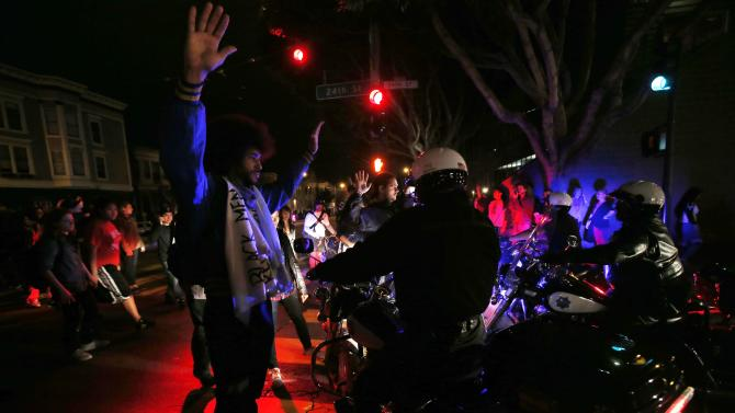 A man raises his hands while attempting to block the movement of a group of motorcycle police during a demonstration against the grand jury decision in the Ferguson, Missouri shooting of Michael Brown in San Francisco