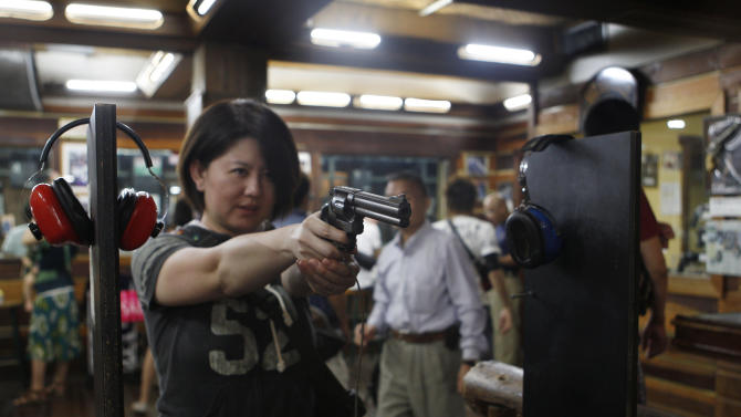 In this photo taken on Saturday, Feb. 2, 2013, Japanese tourist Natsue Matsumoto, 38, warms up for a round of shooting at the Western Frontier Village range in Tamuning, Guam. Gun tourism is a big attraction on the tiny U.S. territory, drawing thousands of visitors who can't own guns in their own countries. For many tourists from Japan, the biggest thrill is the chance to shoot a gun at one of Guam's ubiquitous ranges, dozens of which are tucked between upscale shopping centers. The U.S. territory of Guam - a tropical island often described as a cheaper version of Hawaii - has long been the perfect place to put guns in the hands of tourists, especially from Japan, where gun ownership is tightly restricted and handguns are banned. Despite a shared sense of shock over the recent rampage by a gunman at America's Sandy Hook Elementary School, the gun tourism business here is as brisk as ever. (AP Photo/Eric Talmadge)