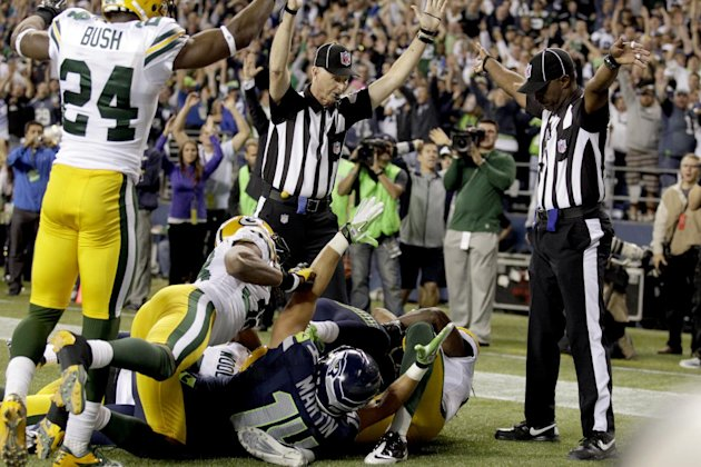 Officials signal a touchdown by Seattle Seahawks wide receiver Golden Tate, obscured, on the last play of an NFL football game against the Green Bay Packers, Monday, Sept. 24, 2012, in Seattle. The Se