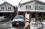 A power line is wrapped around a fallen tree branch on Dawes Road in Scarborough, Monday, December 23, 2013. A day after a severe ice storm hit Toronto, many residents remain without power and downed trees and power lines pose hazards on many streets. THE CANADIAN PRESS/Galit Rodan