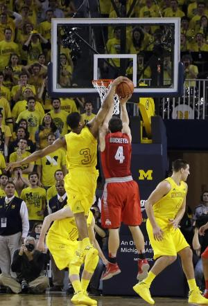 Michigan guard Trey Burke (3) blocks a shot attempt by Ohio State guard Aaron Craft (4) during the overtime period of an NCAA college basketball game at the Crisler Center in Ann Arbor, Mich., Tuesday, Feb. 5, 2013. Michigan defeated Ohio State 76-74. (AP Photo/Carlos Osorio)