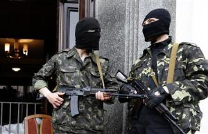 Pro-Russian armed men standb at the entrance to the regional government headquarters in Luhansk