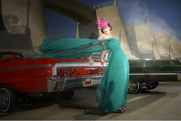 "Catherine models a British couture hat while posing with a vintage American car on ""America's Next Top Model."""