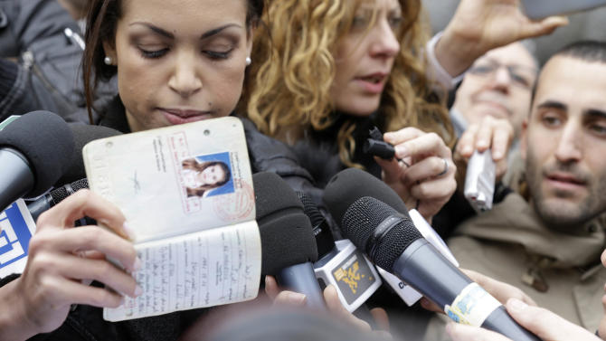 Karima el-Mahroug, also known as Ruby, left, a Moroccan woman at the center of ex-Premier Silvio Berlusconi's sex-for-hire trial, holds up her passport as she is surrounded by reporters outside Milan's court house, Italy, Thursday, April 4, 2013. The Moroccan woman at the center of ex-Premier Silvio Berlusconi's sex-for-hire trial has denounced what she says is psychological warfare being waged against her by Italian prosecutors. Ruby, read out a lengthy statement Thursday to a gaggle of reporters in front of Milan's courthouse denying she was a prostitute and insisting that prosecutors hear her side of the story. (AP Photo/Luca Bruno)