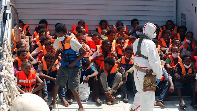 "In this Picture released by the Italian Navy, Monday, Aug. 25, 2014, migrants wait to be boarded on the San Giusto Navy ship, along the Mediterranean sea, off the Sicilian island of Lampedusa, Saturday, Aug. 23, 2014. Italian Interior Minister Angelino Alfano renewed his demand for the European Union to relieve pressure on Italy, which has seen some 100,000 migrants arrive so far this year alone. The country says it spends 9.5 million euros ($13 million) a month to operate the beefed-up air and sea patrols that were launched after more than 360 migrants drowned off the Italian island of Lampedusa last October. ""Italy will make its own decisions"" if EU partners don't offer assistance, he warned in a tweet. The EU's home affairs commissioner, Cecilia Malmstrom, thanked Italy for its ""huge efforts"" to save lives and said in a statement she would meet Wednesday with Alfano ""to better define priorities and provide assistance."" (AP Photo/Italian Navy)"