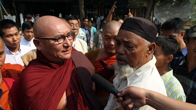 A Myanmar Buddhist monk comforts Muslim refugees, during ethnic unrest between Buddhists and Muslims, as they visit a rescue camp along with Vijay Nambiar, unseen, U.N. Secretary General Ban Ki-moon's special adviser on Myanmar, in Meikhtila, Mandalay division, about 550 kilometers (340 miles) north of Yangon, Myanmar, Sunday, March 24, 2013. Myanmar's army took control of a ruined central city on Saturday, regaining control after several days of clashes between Buddhists and Muslims that killed dozens of people and left scores of buildings in flames in the worst sectarian bloodshed to hit the Southeast Asian nation this year.(AP Photo/Khin Maung Win)